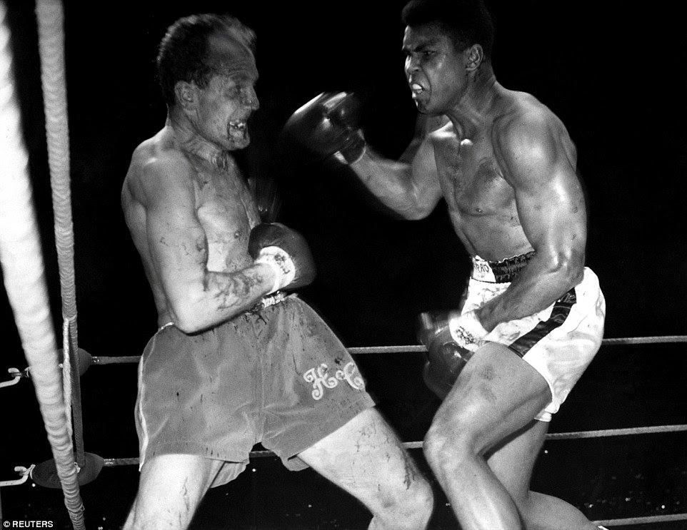 Cooper prepares for another attack from Ali during their bout for the world heavyweight boxing title at Arsenal's Highbury Stadium in 1966. The fight was stopped in the sixth round because of a cut above Cooper's left eye