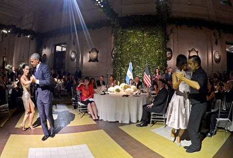 President Obama tangos with a dancer as first lady Michelle Obama tangos with another dancer nearby, during the official state dinner at the Centro Cultural Kirchner in Buenos Aires on March 23, 2016.