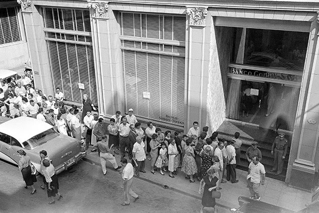 A line of Cubans extending around the corner wait their turn at the Godoy-Sayan Bank in Havana  April 5, 1958 which bore the brunt of heavy withdrawals. Many depositors fearing for the safety of their savings with the treat of civil war hanging over the island republic are withdrawing their savings.