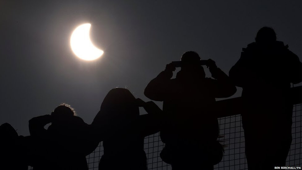 People watch as an eclipse of the sun begins over the Eden Project