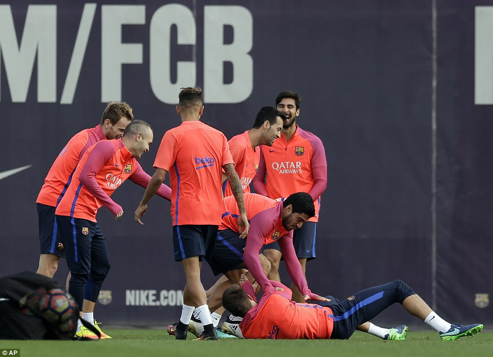 Luis Suarez (centre) jokes with Gerard Pique (laying down) as the training session drill got more intense