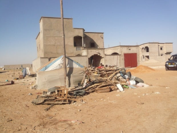 The larger cement home is owned by a private school teacher in Nouchott, Mauritania. He is a slave owner, his slaves - which he calls his guardian family - live in the shack out front.