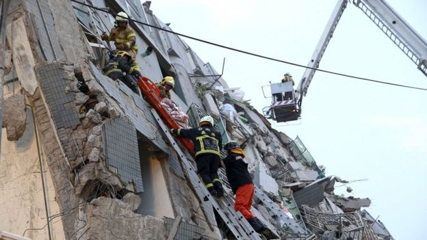 Rescue personnel work on a damaged building