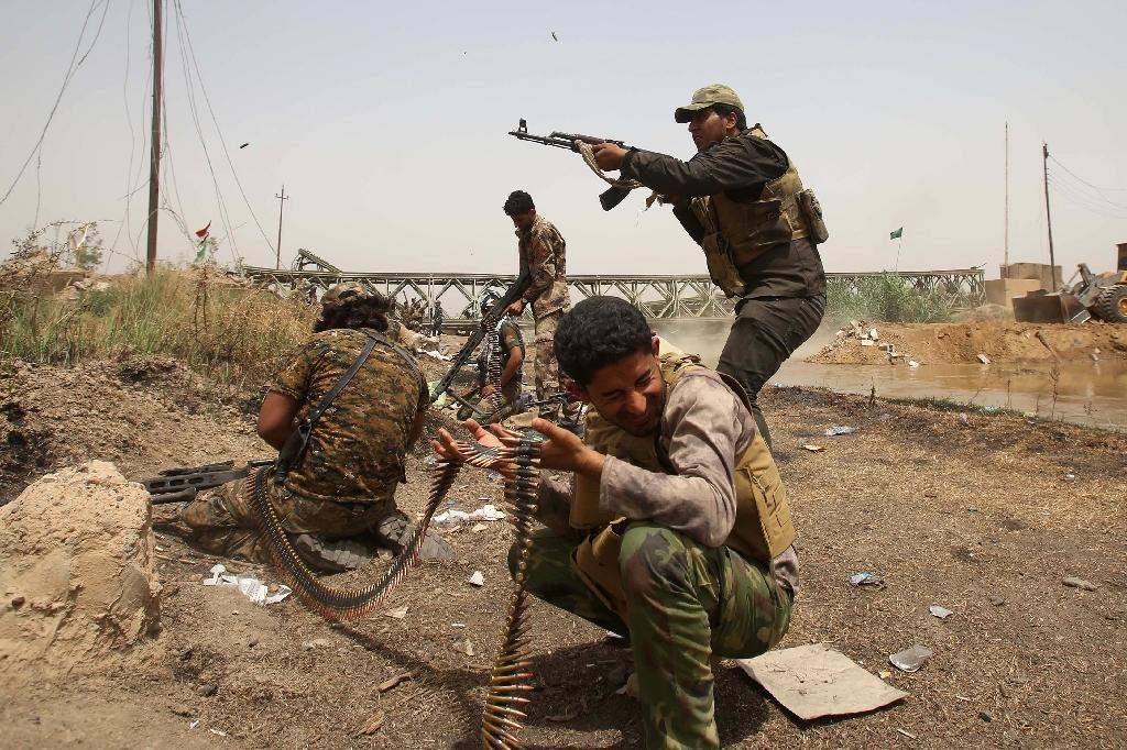 A member of the Popular Mobilisation units opens fire at Islamic State group militants in the area of Sayed Ghareeb, near Dujail, some 70 kilometres north of Baghdad, on May 28, 2015
