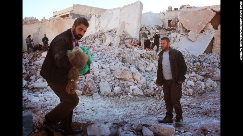 A wounded child is rescued by a White Helmets volunteer after airstrikes on eastern Aleppo Friday.