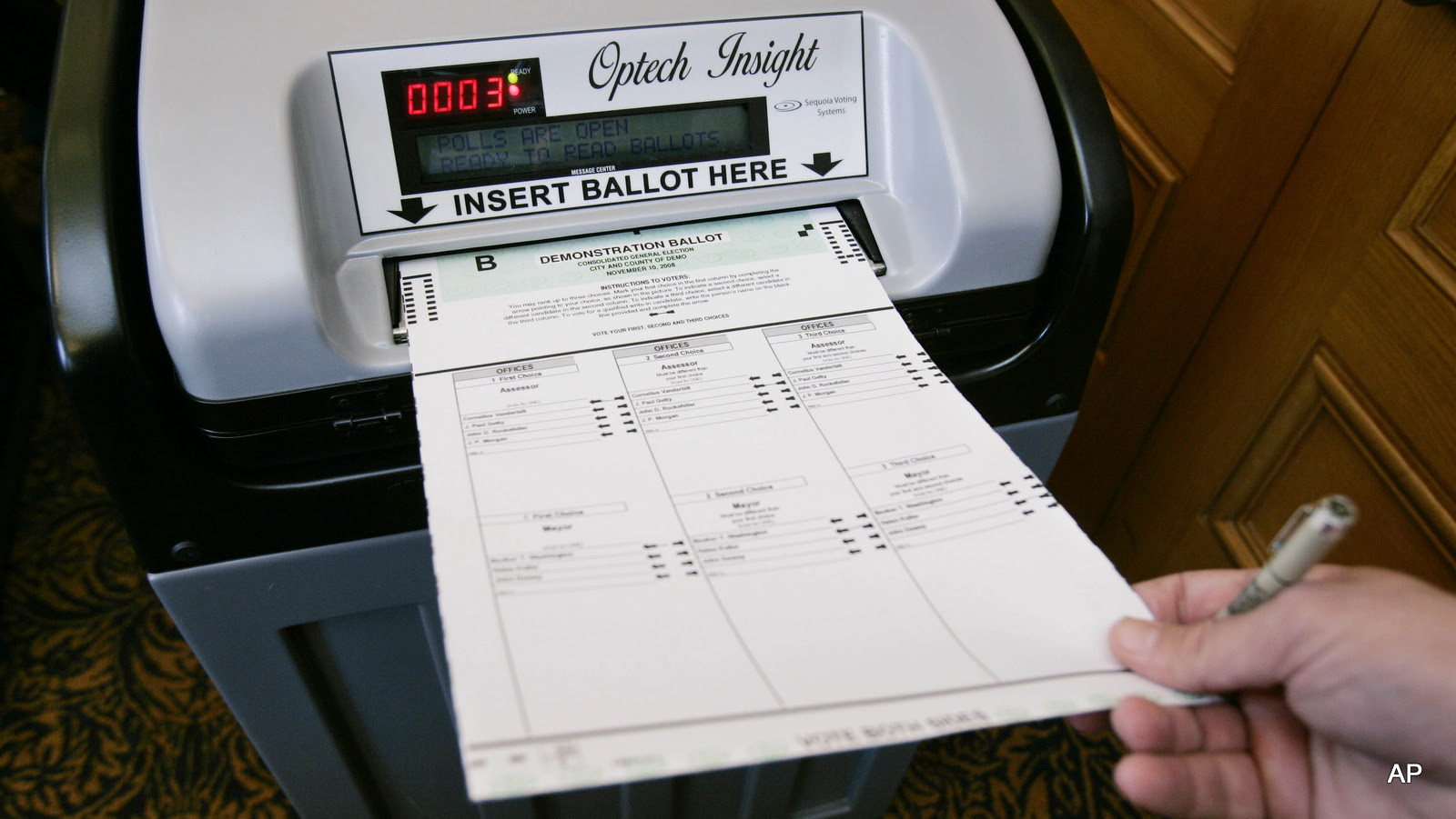 A sales executive with Sequoia Voting Systems demonstrates inserting a ballot into their electronic voting system for officials in San Francisco, Dec. 5, 2007