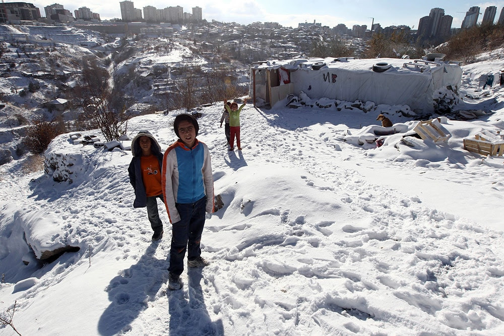 Syrian refugees pose in the snow in front of their makeshift home in Ankara. (ADEM ALTAN/AFP/Getty Images)