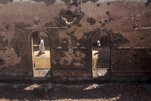 Egyptians walk in the ruins of the Evangelical Church…