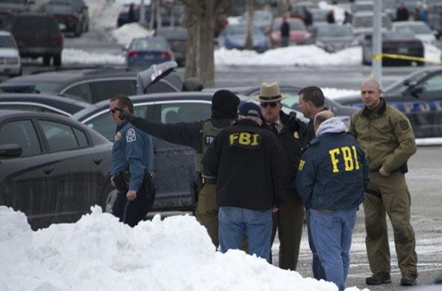 Membros do FBI e policiais locais conversam em frente ao shopping Columbia Mall, onde três pessoas morreram em tiroteiro registrado neste sábado (25) (Foto: Jim Watson/AFP)