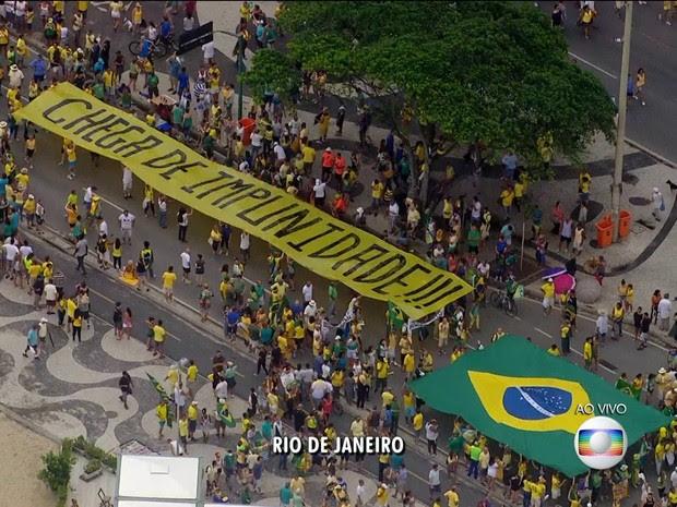 """MANIFESTAÇÃO/RIO (12H41): Bandeirão com dizer """"chega de impunidade"""" é carregado por diversas pessoas no ato em Copacabana. (Foto: Reprodução / TV Globo)"""