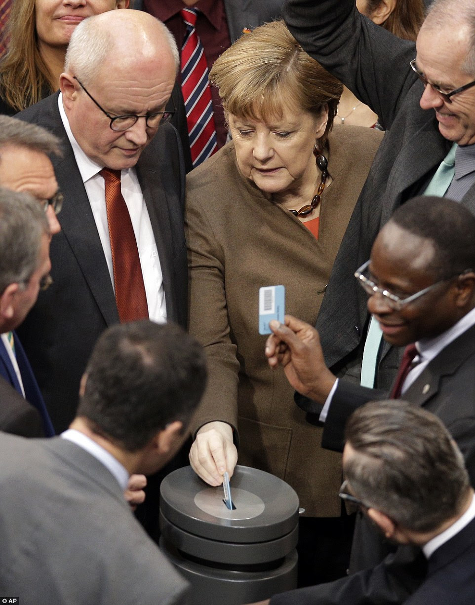 German Chancellor Angela Merkel (centre) casts her vote during an asylum debate as part of a meeting of the German Federal Parliament, Bundestag, at the Reichstag building in Berlin, Germany today