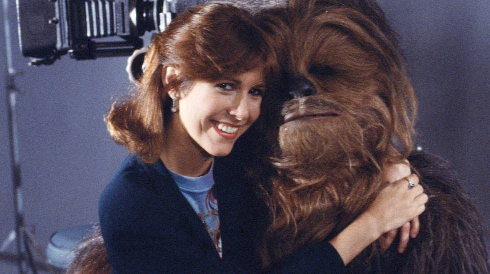 La actriz Carrie Fisher junto a Chewbacca, durante el rodaje de la segunda película de Star Wars en 1983.