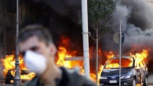 Homem caminha ao lado de carros em chamas durante a 'Marcha dos indignados', em Roma (Foto: Max Rossi/Reuters)