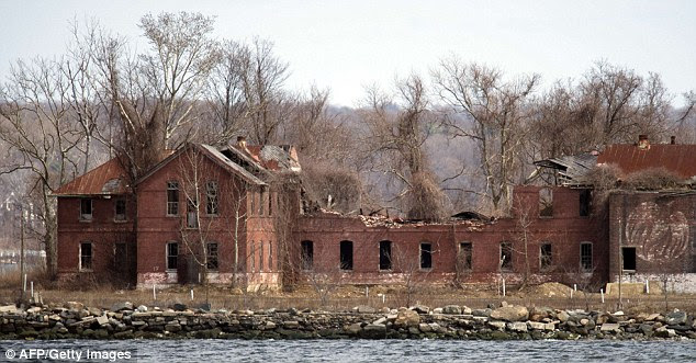 Forbidden: Access to Hart Island and its decaying abandoned prison workhouse is severely restricted. Each white plastic pipe near the building marks an infant mass gravesite, one plastic pipe per 1,000 babies