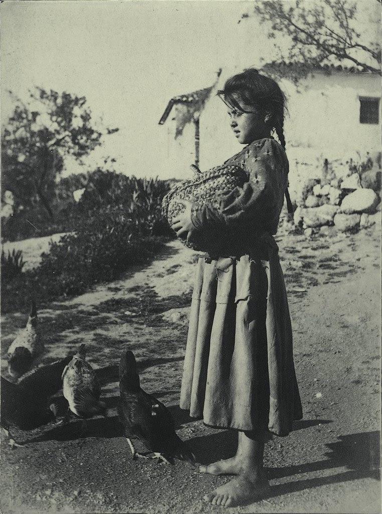 Niña alimenta gallinas a comienzos del siglo XX. Fotografía de Pedro Román Martínez. Centro de Estudios Juan de Mariana. Diputación de Toledo