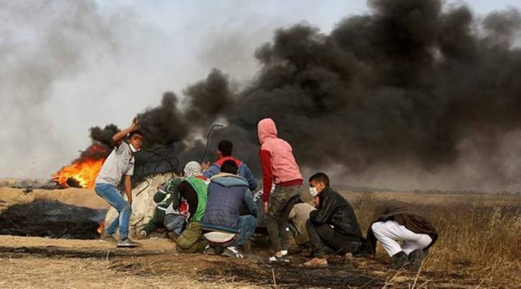 Palestinian protesters cover during clashes with Israeli troops along Gaza's border with Israel on Thursday. (AP)