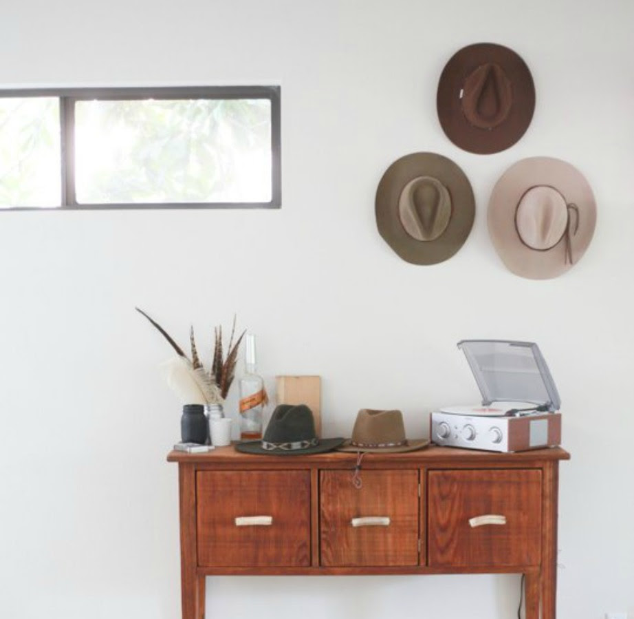 Τα τρία καπέλα στον τοίχο δημιουργούν ένα πιο ισορροπημένο αποτέλεσμα, από το να ήταν απλά δύο καπέλα κρεμασμένα.
