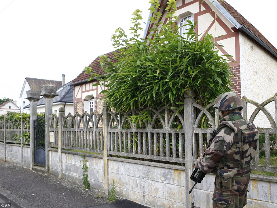 A French soldier stands guard as he prevents the access to the scene of the attack in Saint-Etienne-du-Rouvray, Normandy, France