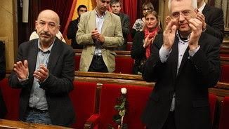 Els diputats de Junts pel Sí Germà Bel i Josep Maria Forné aplaudeixen en memòria de Muriel Casals, després de deixar una rosa blanca al seu escó (ACN)