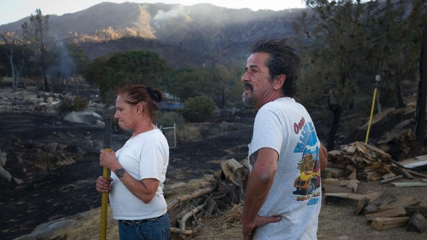 June 24, 2016: Rick Gutierrez, right, and wife, Jean, take a short break while putting out hotspots on their neighbor's property near Mountain Mesa, Calif.