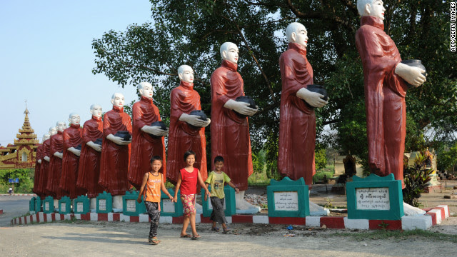 Children walk past giant statues of monks at a pagoda in the town of Myitkyina, in Kachin province in May 2012.