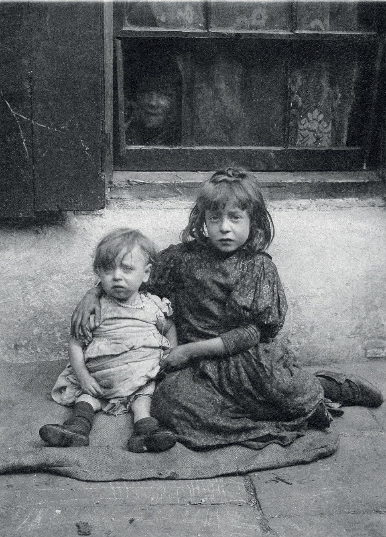 Ragamuffins: Annie, siete, y un año de edad, Nellie, se sientan tristes y hambrientos en el despido fuera de su casa en Spitalfields.  Estaban entre diez niños nacidos de madre soltera Annie Daniels.  Cinco de sus hermanos murieron en la infancia