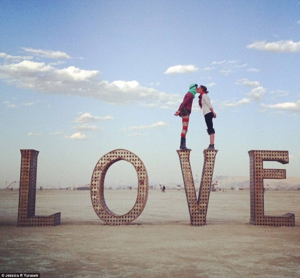 V. romantic: A couple kisses on top of the letter V on Wednesday at Burning Man