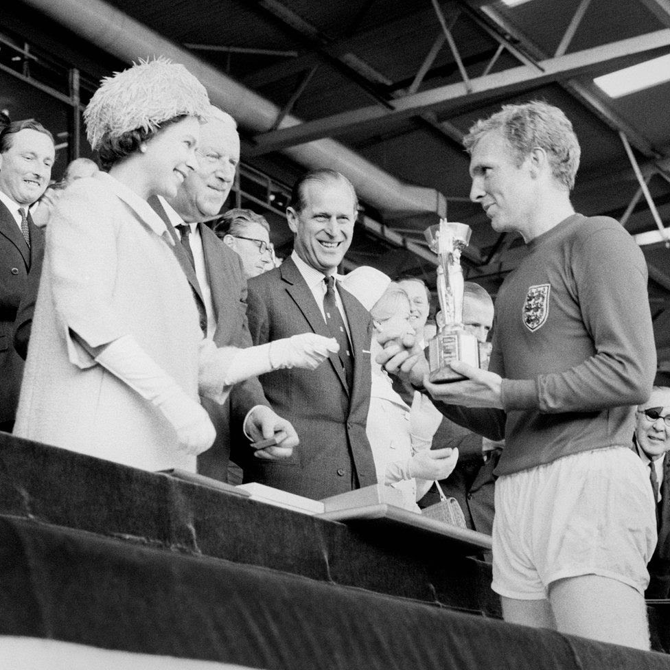England captain Bobby Moore holds the Jules Rimet Trophy, collected from the Queen Elizabeth II