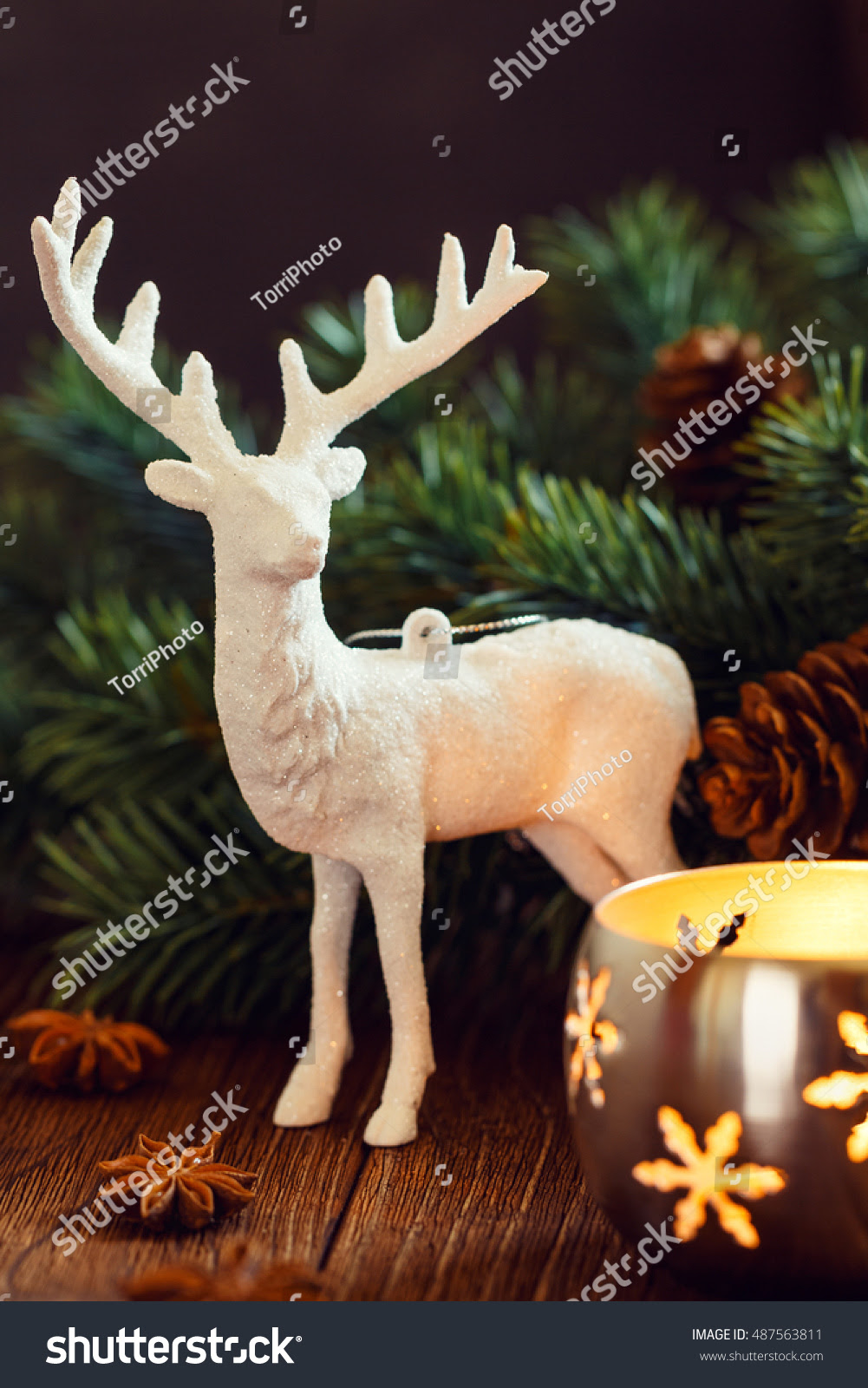 White deer Christmas decoration on rustic background with candle lantern and fir branch