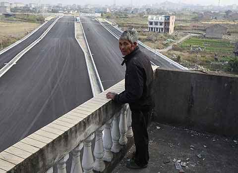 Luo Baogen olha para a estrada que ainda está para ser inaugurada (Aly Song)