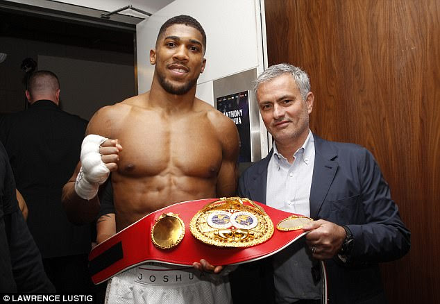 IBF heavyweight champion Anthony Joshua celebrates his win with Jose Mourinho backstage at the O2 Arena