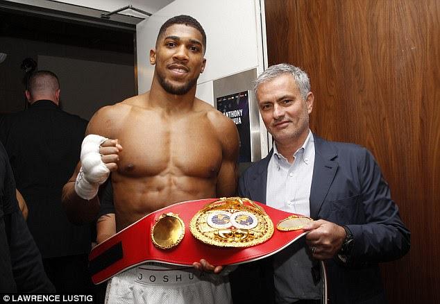 IBF heavyweight champion Anthony Joshua celebrates his win with Jose Mourinho backstage at the O2 Arena