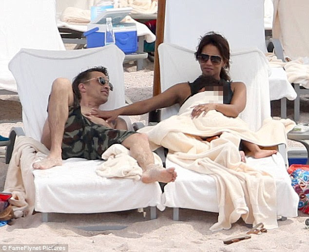 Is the divorce still on? Halle Berry laid a hand on Olivier Martinez's bare chest over his heart on Tuesday as they lounged on the beach during a getaway to Puerto Vallarta, Mexico with their kids