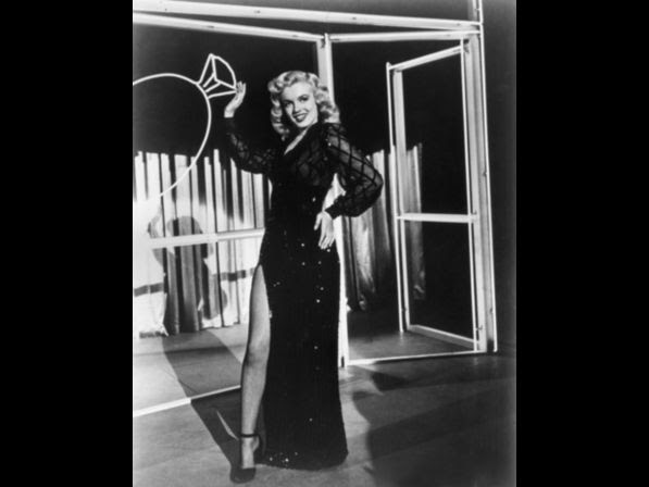 Monroe wearing an evening dress with a high slit revealing a fishnet stocking, standing in front of a neonlit set with an image of a diamond ring in a still from director Phil Karlson's film, 'Ladies of the Chorus'.