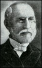 Head shot of balding gentleman with neatly  trimmed white hair, moustache and beard, wearing glasses.