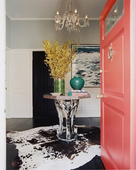 A pink front door opening into a foyer with a hide rug and an octagonal table