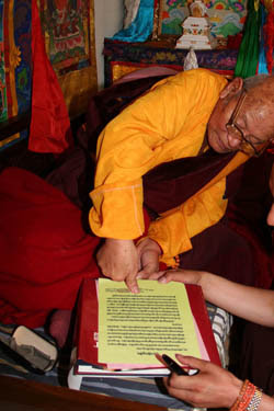 Dorje Rinzin Rinpoche, master of the seventh Dzogchen Dharma King in China, stamps his fingerprint onto the congratulatory letter he wrote to H.H. Dorje Chang Buddha III