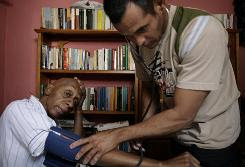 Physician Ismely Iglesias checks Cuban dissident Guillermo Farinas' blood pressure last week. Farinas has since been taken to the hospital by relatives.