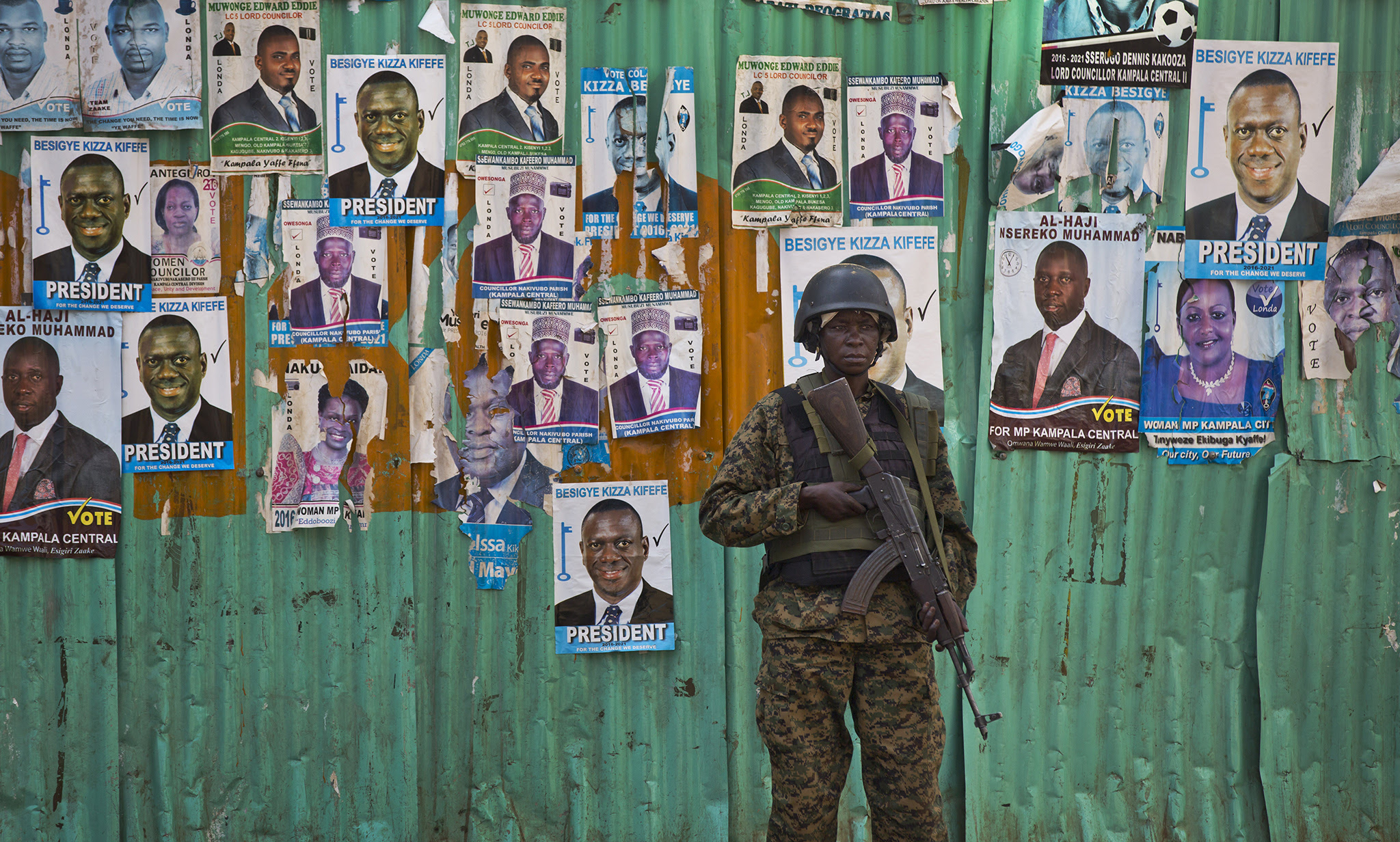 A Ugandan soldier stands guard in front of posters for opposition leader Kizza Besigye and other candidates fin the parliamentary elections