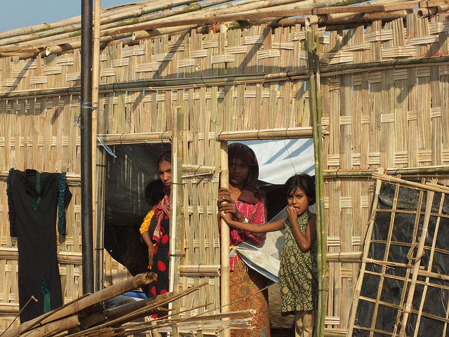 Rohingya women stand next to their partially constructed new home in Kutupalong camp, Bangladesh. Credit: Naimul Haq/IPS