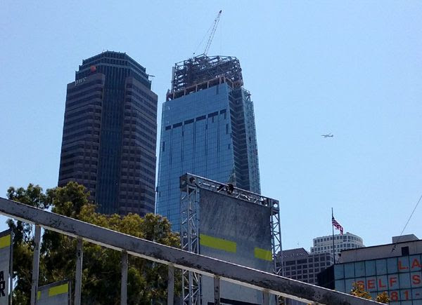 An airliner sails through clear blue skies above the Wilshire Grand Center on August 23, 2016.