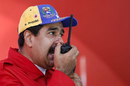 Venezuela's President Nicolas Maduro speaks on a walkie talkie during a visit to inspect the progress of a Metrocable station and a meeting with supporters in the Petare slum district of Caracas December 1, 2015. REUTERS/Carlos Garcia Rawlins