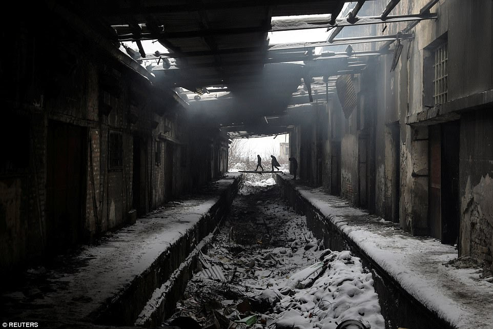 Migrants walk during a snowfall inside a derelict customs warehouse in Belgrade, Serbia, on January 11. A squalid camp in the city was nicknamed the 'new Calais' after the so-called Jungle in France, where migrants flocked during the global crisis