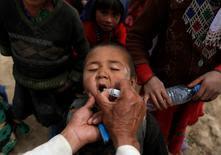 Un niño afgano recibe la vacuna contra el polio cerca del distrito de Argo, en la provincia de Badakhshan, 4 de mayo de 2004.  El virus de la polio fue encontrado en muestras tomadas en aguas residuales cerca de Sao Paulo, una de las ciudades sedes de la Copa Mundial de Fútbol, pero hasta ahora no se han reportado casos de la enfermedad en humanos, informó el lunes la Organización Mundial de la Salud (OMS). REUTERS/Mohammad Ismail