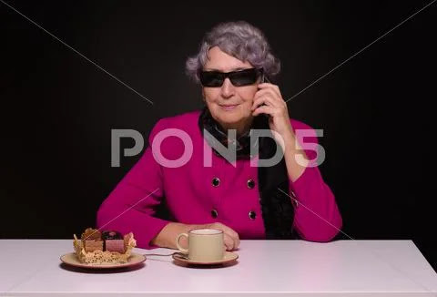 Grayhaired woman in sunglasses talking on a cell phone