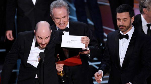 As Warren Beatty and Oscars host Jimmy Kimmel look on, LA LA LAND producer Jordan Horowitz announces that MOONLIGHT won Best Picture...on February 26, 2017.