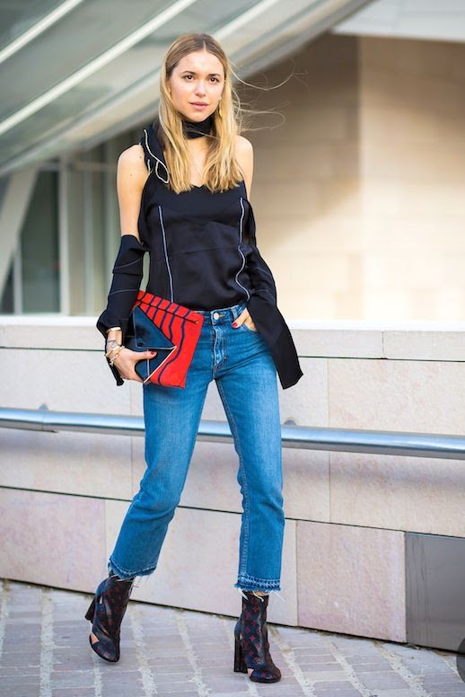 Le Fashion Blog Pfw Street Style Pernille Teisbaek Black Deconstructed Top With A Wrapped Neck Open Shoulders And Draped Sleeves Red Clutch Cropped Jeans With Raw Hems Louis Vuitton Ankle Boots Via Style Du Monde