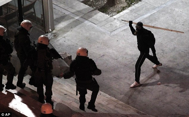 Austerity anger: A protester attacks police during a demonstration in Athens' main Syntagma square last night as the Greek parliament prepares to vote on cuts needed before a £108bn EU bailout