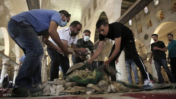 Palestinians clean up debris inside Al-Aqsa mosque in Jerusalem's Old City after clashes at the compound between Palestinians and Israeli police on September 13, 2015, just hours before the start of the Jewish New Year. The disturbances came with tensions running high after Israeli Defence Minister Moshe Yaalon last week outlawed the Murabitat (for females) and Murabitun groups which are made up of east Jerusalem Palestinians and Israeli Arabs and who confront Jewish visitors to the volatile Al-Aqsa mosque complex, considered Islam's third holiest shrine. AFP PHOTO / AHMAD GHARABLI        (Photo credit should read AHMAD GHARABLI/AFP/Getty Images)