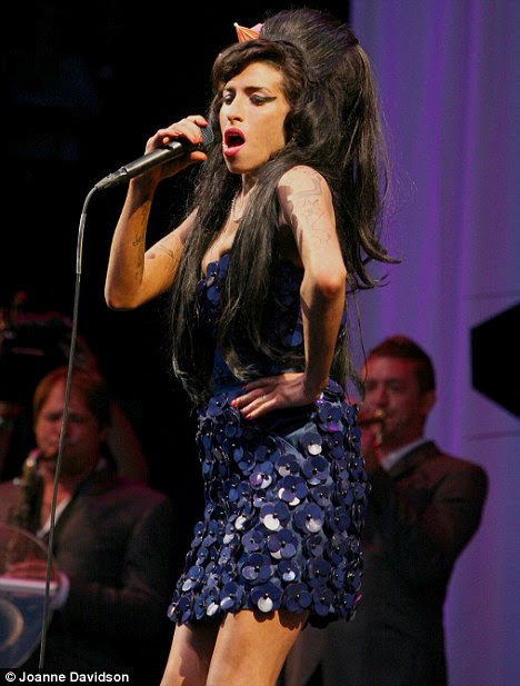 Singing sensation: Amy had huge hits with tracks including Rehab and Back To Black and is seen here performing at Glastonbury in 2008